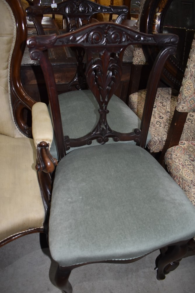 A pair of carved back dining chairs having carved legs