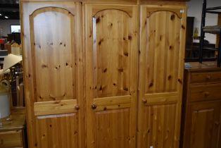 A modern pine triple wardrobe having drawer base