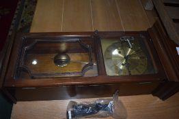 A reproduction mahogany effect wall clock , having brass Metamec face