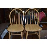 Two light stained hoop back dining chairs
