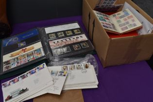 A box containing GB First Day Covers, an Album of Presentation Packs and five Albums of World Stamps