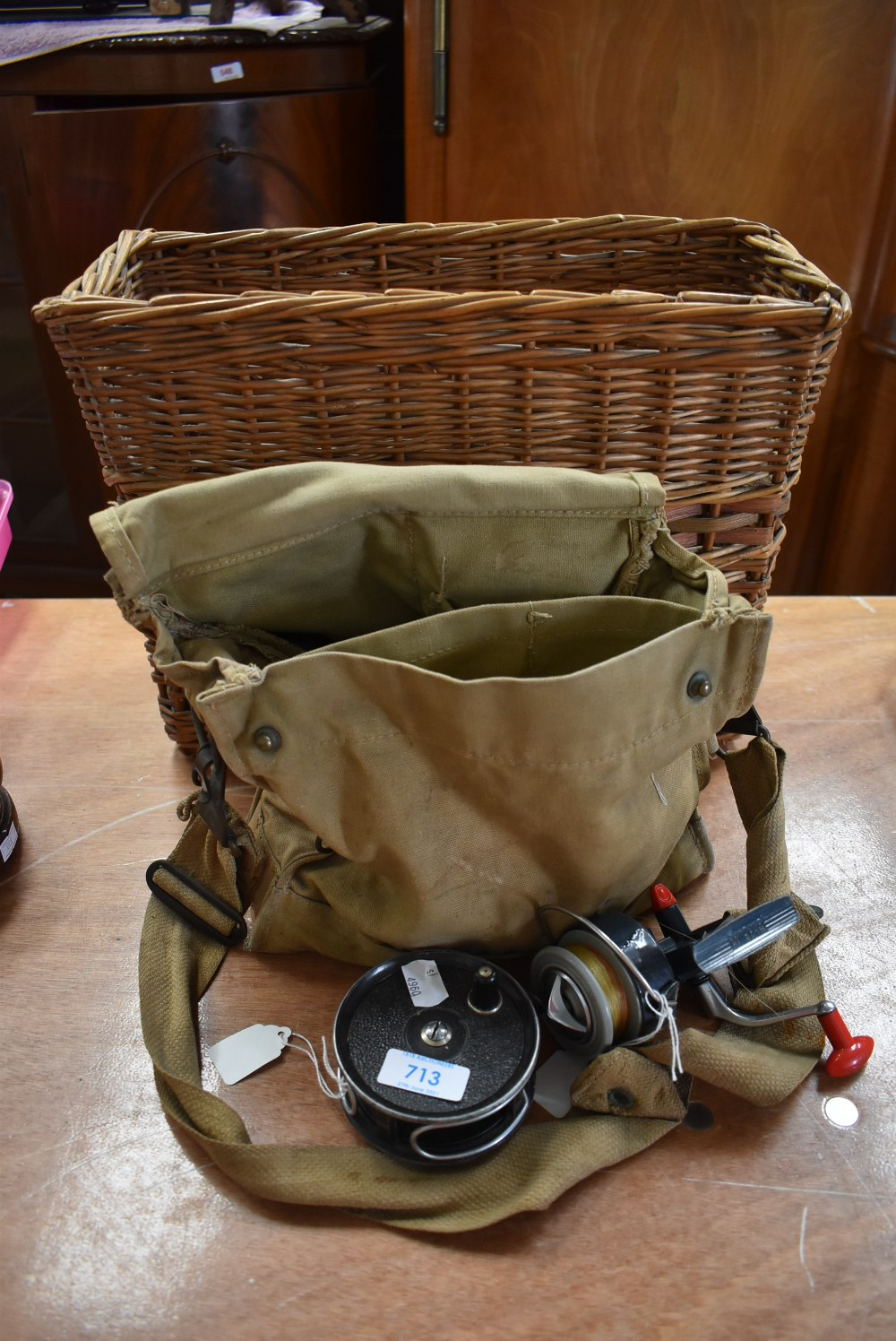 A wicker basket containing canvas bag with tackle and two reels.
