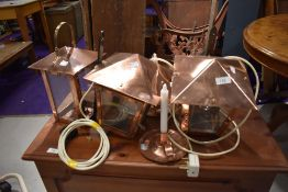 Three copper wall lights, lantern style, and a pair of copper candlesticks