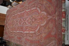 A very large wool Victorian Paisley shawl in reds,blues,browns and greens with fringed edge.some