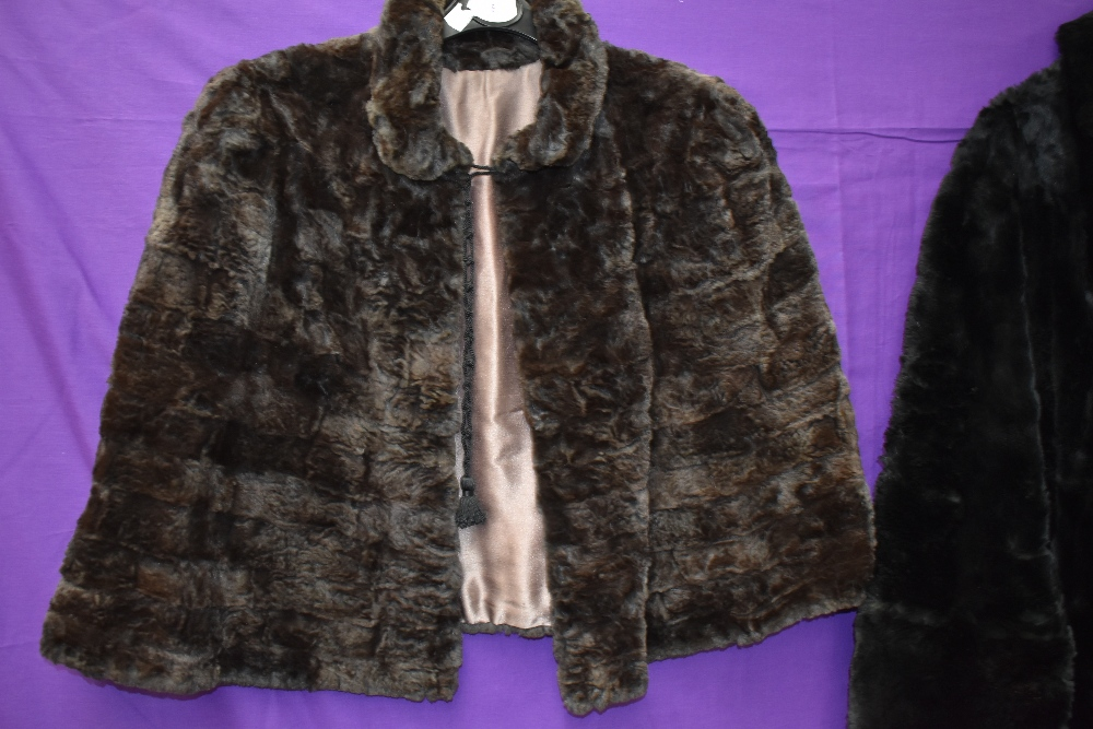 A black 1940s fur coat having pom pom fastenings and a 1940s brown mole skin cape. - Image 2 of 3