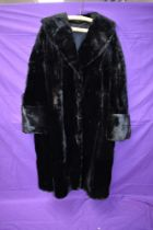 A striking vintage black fur coat having wide sleeve openings with turn up and shawl collar,serviced