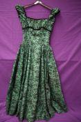 A green Rosecroft model 1950s gown having flocked floral detailing,velvet trim to under bust, sleeve