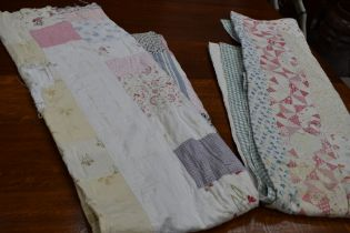 A large vintage quilt using a variety of cotton sections in various colours and patterns, some