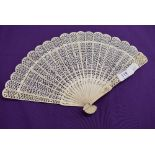 An intricate antique fan having carved ribs and mother of pearl rivet.