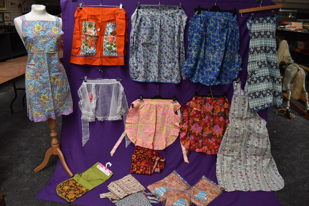 A lovely collection of aprons and overalls, some having original packaging and a lot appearing