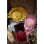 A suitcase containing an assortment of vintage hats and a fur stole, various eras and styles.