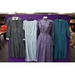 A collection of vintage and retro Laura Ashley dresses in a mixture of colours and styles.
