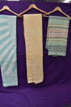 Three vintage bed throws, one yellow and white, another green and white and a striped one in green