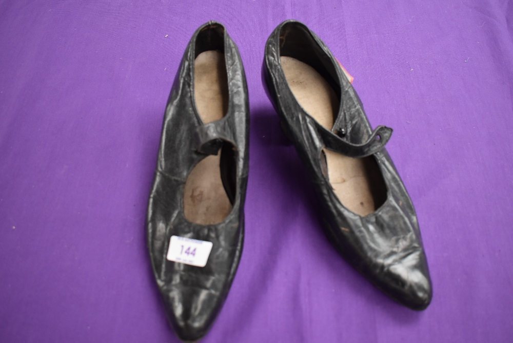 A pair of antique black leather shoes.