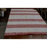 A large red and white patchwork quilt, having different patterns to front and reverse, some age