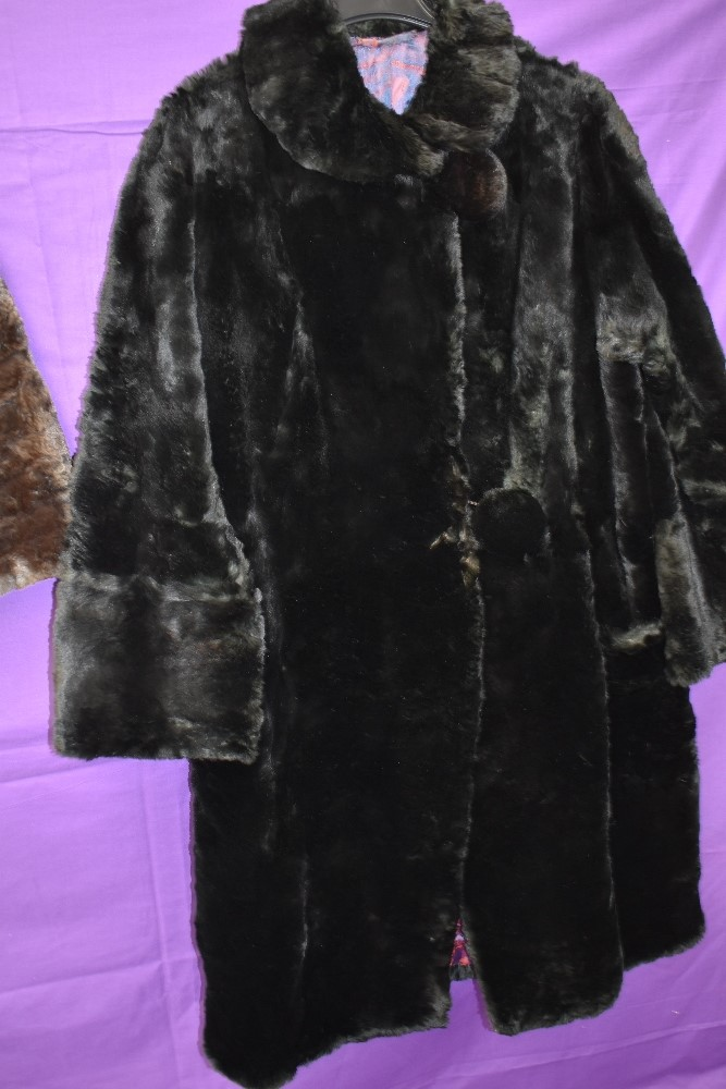 A black 1940s fur coat having pom pom fastenings and a 1940s brown mole skin cape. - Image 3 of 3