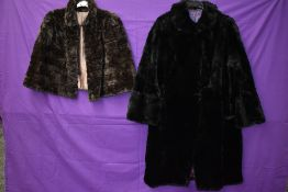 A black 1940s fur coat having pom pom fastenings and a 1940s brown mole skin cape.