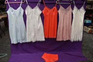 A collection of vintage nylon slips in a variety of colours, one having matching knickers.