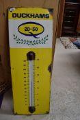 An enamel garage advertising sign thermometer for Duckhams Oil