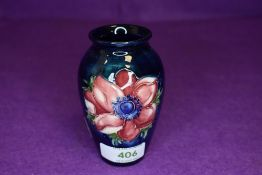 A small size Moorcroft vase having deep blue ground with Anemone design 10cm tall