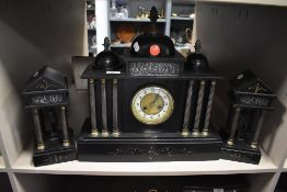 A slate mantel clock with matching garnitures