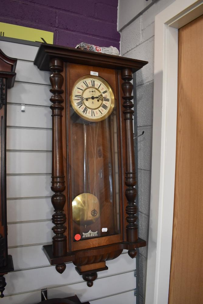 A British enamelled faced wall clock having weighted pendulum in mahogany case