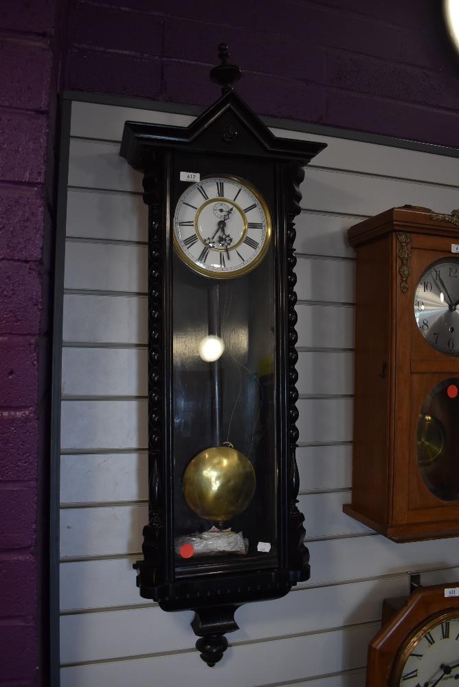 An enamel faced wall clock having single weight pendulum