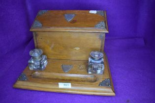 A golden oak Edwardian writers compendium or desk tidy having double ink well