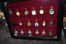 A glazed display case containing eighteen pocket watches or time pieces