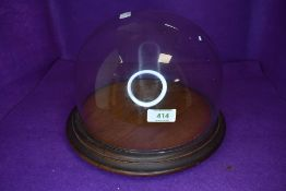 A cheese board or similar cake stand having glass dome top with oak plinth