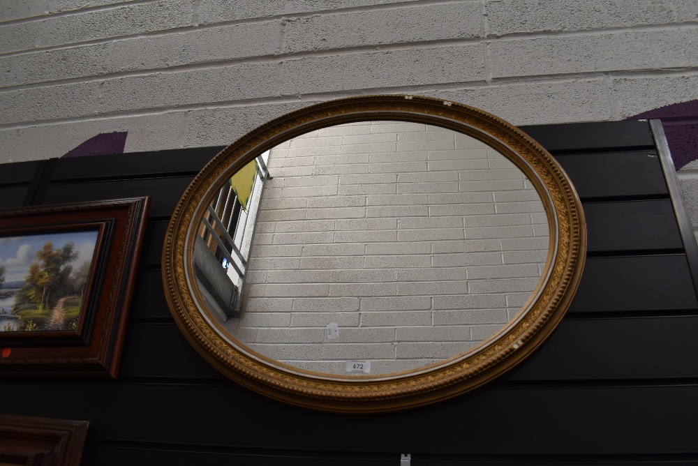 An oval framed gilt and gesso mantle mirror
