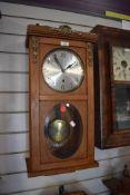 A wood framed wall clock with pendulum