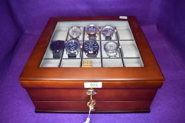 A 15 space watch box with lower drawer and lock containing eight gent's fashion wrist watches
