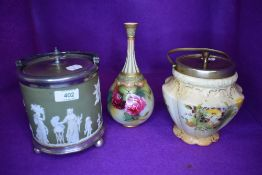 A biscuit barrel in a Jasper ware design with light green ground, a similar biscuit barrel and a