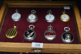 A glazed display case containing eight pocket watches or time pieces