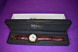A gent's wrist watch by Stauer no:DS13373 having day, date, month and moon phase dials to face and