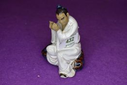 A vintage Chinese figure of a man playing instrument in a mudman style signed Wan Jiang to base
