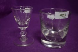 An antique heavy set whisky tumbler etched J Spink and Sons and similar baluster stem wine glass