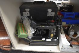 A fine example of a 222k portable sewing machine by Singer with case etc