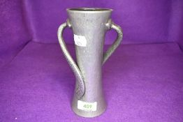 An arts and crafts style Tudric pewter vase having hammered body with double twist arms 17cm tall