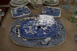Four antique blue and white ware willow pattern charger and meat drainers large oval having stains