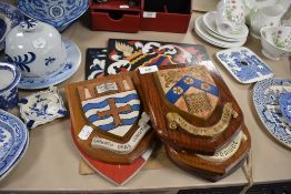 Five oak and hand painted crest shields and two similar hand painted motto crests