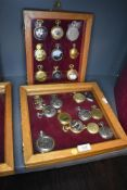 Two glazed display cases containing twenty one pocket watches or time pieces