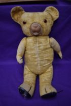 A mid 20th century straw filled teddy bear having plastic eyes, rubber nose and mouth, padded paws