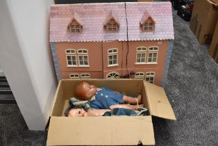 A modern wooden two storey dolls house having plastic and wooden furniture and accessories along