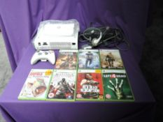 A Microsoft Xbox 360 console with one controller, power cable, head set and instruction booklet