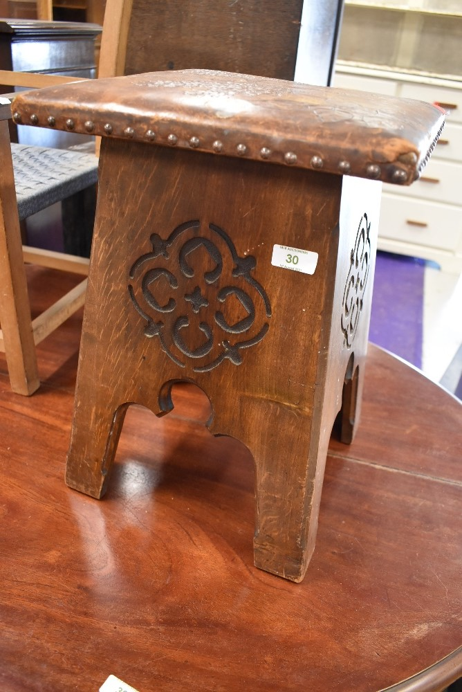 An arts and crafts stool having carved sides with decorative leather worked top