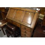 An early 20th Century oak bureau having panelled flap, interesting compartmental interior , heavy