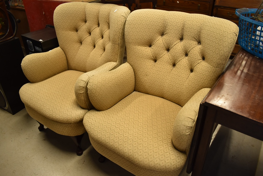 A pair of traditional easy chairs , having button backs on cabriole legs