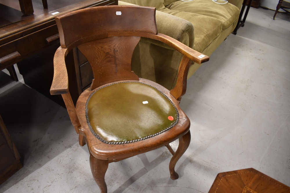 An early 20th Century oak office armchair having shaped legs and double stretcher